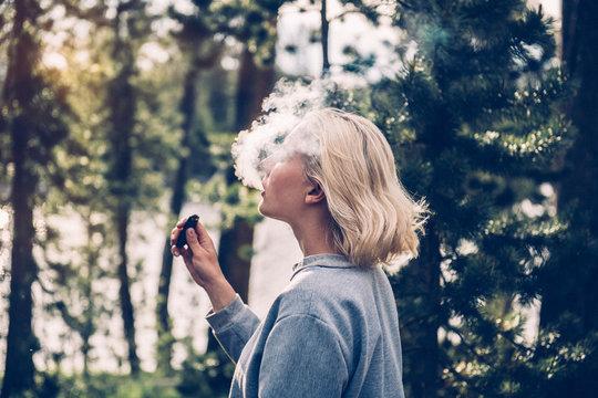 Beautiful woman smokes electronic vape cigarette blowing white smoke in a forest