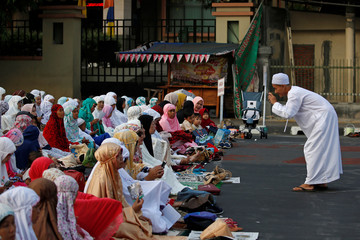 Indonesian Muslim man takes pictures as he attends Eid al-Adha prayers on a street in Jakarta