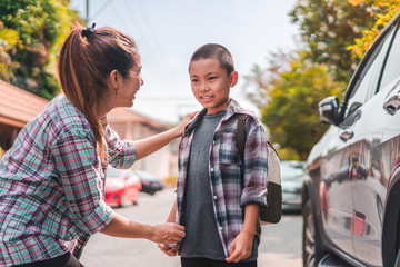 Beautiful young asian mother or parent helping son or pupil to getting in the car to ride to school, Selective focus, Back to school concept.