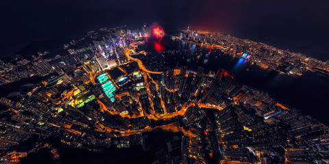 Fototapete - Panorama aerial view of Hong Kong City at night with fireworks