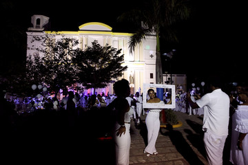 An attendee poses for a picture, with the Cathedral of Cap Haitien in the background, during 2019 Haiti Diner en Blanc event in Cap Haitien