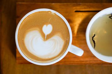 Foto op Plexiglas Chocolade Heart-shaped coffee on a brown wood table