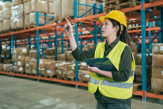 attractive woman in warehouse checking inventory levels of goods on shelf. lady worker in hard hat and safety vest point finger looking up counting parcels and cardboard boxes in large storehouse.