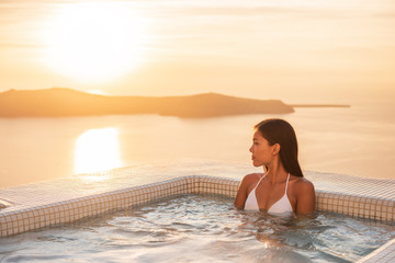 Wall Mural - Luxury resort woman swimming in jacuzzi hot tub outside on private hotel room balcony watching sunset over Mediterranean sea. Europe honeymoon vacation.