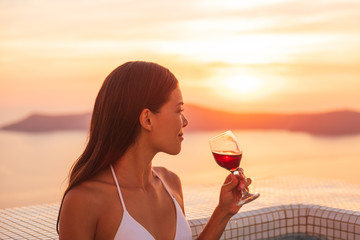 Wall Mural - Luxury vacation woman drinking red wine glass in private jacuzzi at luxury hotel destination. Santorini europe getaway Asian girl relaxing in bikini swimming in pool.