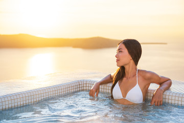 Wall Mural - Luxury hotel travel woman in spa pool hotel with Mediterranean sea background. Santorini vacation summer holidays girl enjoying holiday getaway. Asian model relaxing.