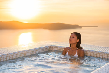 Wall Mural - Spa hotel luxury relax jacuzzi therapy pool Asian woman relaxing in resort hot tub outside on private room balcony sunset over sea. Europe honeymoon vacation relaxation wellness pampering.