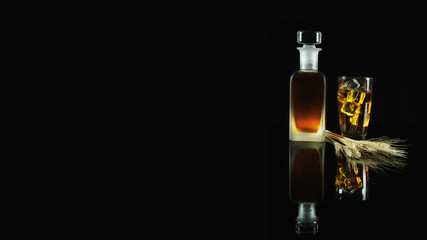 a glass of iced whisky and a bottle of whisky with wheat on reflected floor on dark background