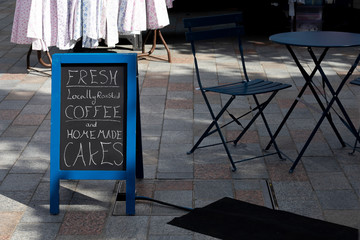 marketplace cafe advertising board promoting fresh locally roasted coffee and homemade cakes