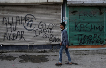 A Kashmiri boy walks past the graffiti written on the shutters of closed shops during restrictions after the scrapping of the special constitutional status for Kashmir by the government, in Srinagar