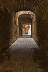 Architectural details of medieval stone and brick houses in a narrow passages at Volterra, Tuscany, Italy
