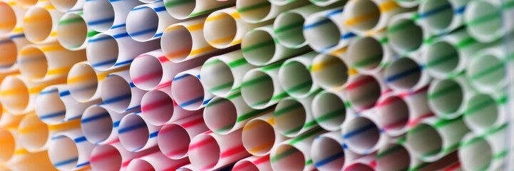 Panoramic colorful background of many drinking plastic straws