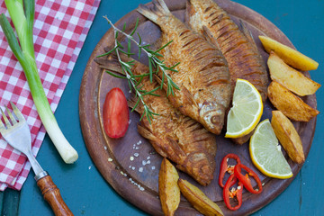 Fried fish served on a wooden plate with potato and decorated with rosemary and lemon. Healthy lunch in nature.Top view.