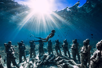 Woman freediver with fins dive near underwater statues. Underwater tourism in the ocean.