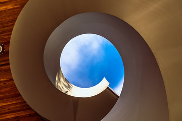 A spiral staircase leading to a blue sky at a public access garden in Docklands, Melbourne, Australia