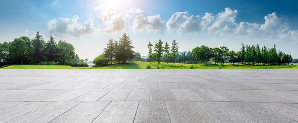 Empty square floor and green woods natural scenery in city park Wall mural