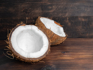 Two halves of fresh coconut on a dark wooden background. Copy space.