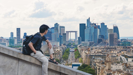 Wall Mural - a man with backpack looking at Paris cityscape in France