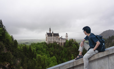 Wall Mural - a man with backpack traveling at Neuschwanstein Castle, famous place and travel destination in Fussen, Germany