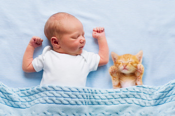 Baby boy sleeping with kitten. Child and cat.