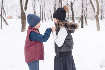 brother and sister students having fun after school on a snowy day. a schoolgirl and a schoolboy playing together in winter