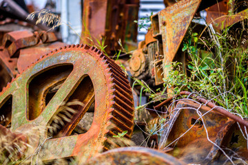 Large abandoned machine cogs are left to rust and decay in a junkyard.