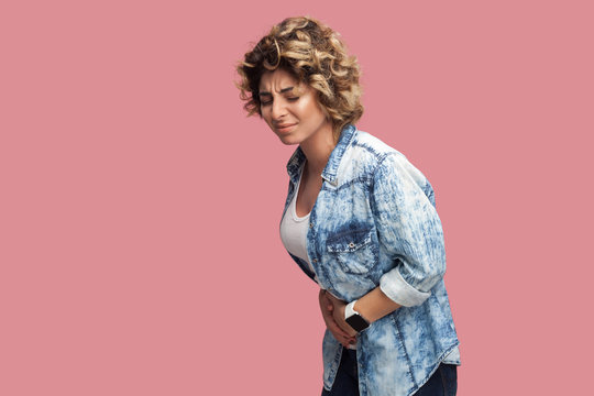Stomach pain. Profile side view portrait of upset young woman with curly hairstyle in casual blue shirt standing and holding her painful belly. indoor studio shot, isolated on pink background.
