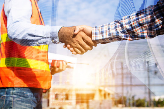 Architect contractor shaking hands with client at construction site