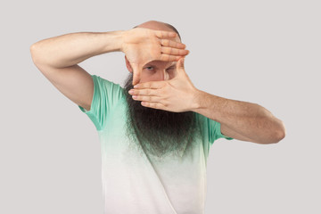 Portrait of attentive middle aged bald man with long beard in light green t-shirt standing with crop composition gesture and looking through hands. indoor studio shot, isolated on grey background.