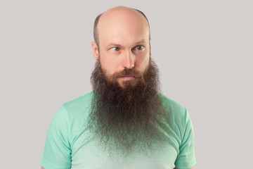 Portrait of crazy middle aged bald man with long beard in light green t-shirt standing and looking with croosed eyes funny face. indoor studio shot, isolated on grey background.