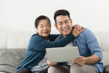 Asian man teaching his mother using laptop at home, technology concept.