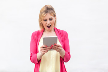 No way! Portrait of beautiful unbelievable young woman in pink blouse standing and watching suprised video on her tablet with shocked face. Indoor, isolated, studio shot, white background