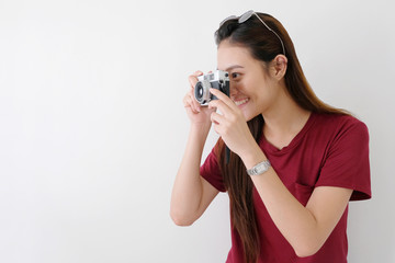 Young happy asian woman tourist holding camera standing over white wall background with copy space, Asian traveler girl smiling while holding vintage camera on vacation