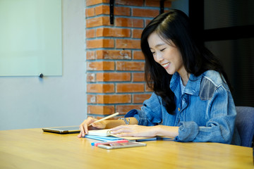 Asian woman university student in casual writing on paper notebook, Teenager student hand writing lecture note book at school campus, College, university education