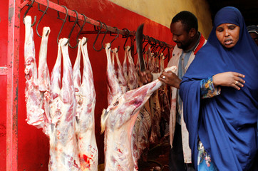A Muslim woman shops for goat meat inside a slaughterhouse during celebrations marking the Muslim holiday of Eid al-Adha at an open field in Nairobi