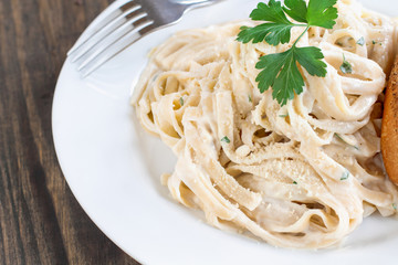 Plate of fettucini alfredo with fresh parsley and a slice of french bread. Top view.