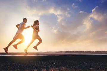 Foto auf AluDibond Jogging Young couples running sprinting on road. Fit runner fitness runner during outdoor workout with sunset background