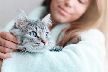 Beautiful woman at home holding and hug her lovely fluffy cat. Gray tabby cute kitten with blue eyes. Friend of human. Good sunny morning. Fototapete
