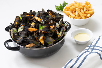Belgian mussels with potato fries and sauce on white marble table