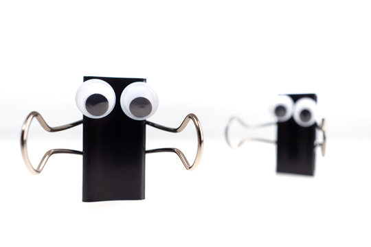 Emoji. Paper clips with bulging eyes. Emoji hugs. One ???????? creeps up to the other from behind. Smiley - hugs. Stationery clothespins pulled his hands. Hello smiley. Concept office workers.