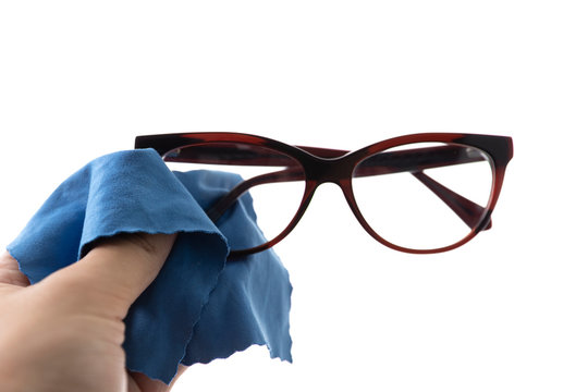 Close-up of a hand with a blue cloth that wipes the glasses. Isolated