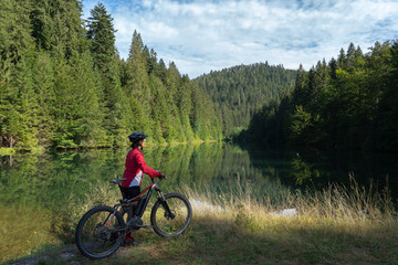 nice and ever young senior woman with her electric mountain bike at the Kinzig drinking Water reservoir in the northern Black Forest, Baden-Wuerttemberg, Germany