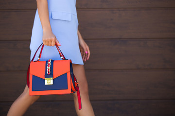 Stylish blue with orange leather women bag. The girl holds in her hand. Young woman walking down the street with a bag. Bag close up.