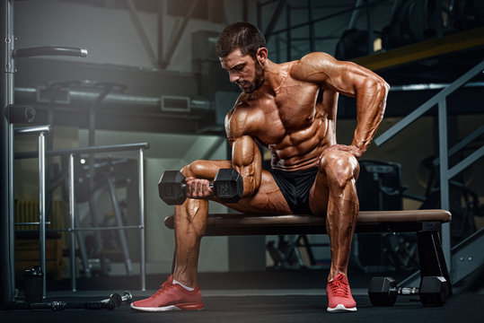 Muscular Men Exercise With Weights. Performing Dumbbell Bicep Curls