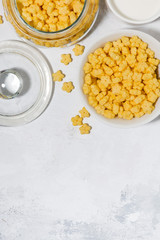 breakfast cereal for children - crispy stars on white background, vertical top view