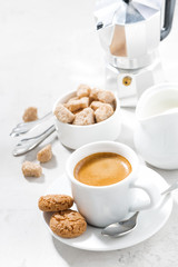 cup of espresso and sweet cookies on a white table, vertical top view