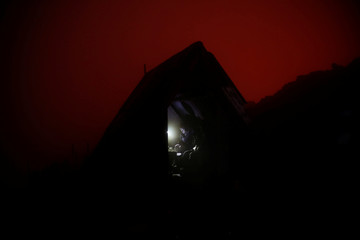 The red glow of the lava lake is seen as a Virunga park employee sits in a shelter on the edge of Nyiragongo volcano's crater inside the Virunga National Park near the eastern Congolese city of Goma