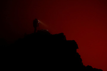 A tourist takes pictures of the lava lake from the edge of the crater of the Nyiragongo volcano inside the Virunga National Park near the eastern Congolese city of Goma