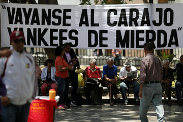 """People sit in front of a banner reading """"Go to hell shitty yankees"""" at Bolivar Square in Caracas"""