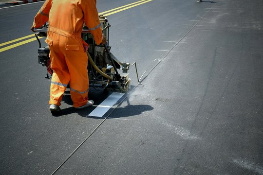 Road worker using thermoplastic spray road marking machine to painting white line on asphalt street